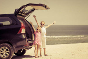 Kids stood by car at beach