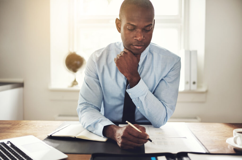 executive sitting at desk and reviewing employees benefit plans